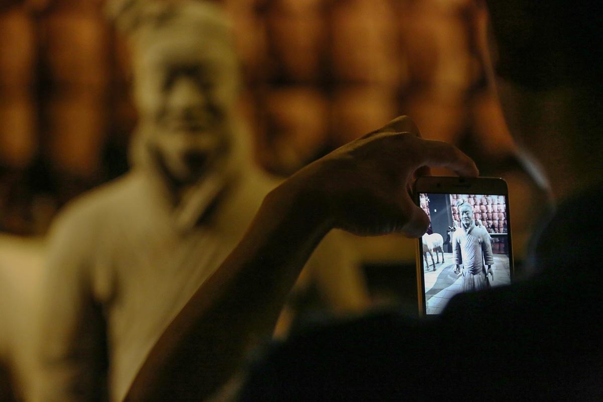 考察团成员在陕西省历史博物馆使用荣耀6Plus拍摄兵马俑。摄影:孟菁