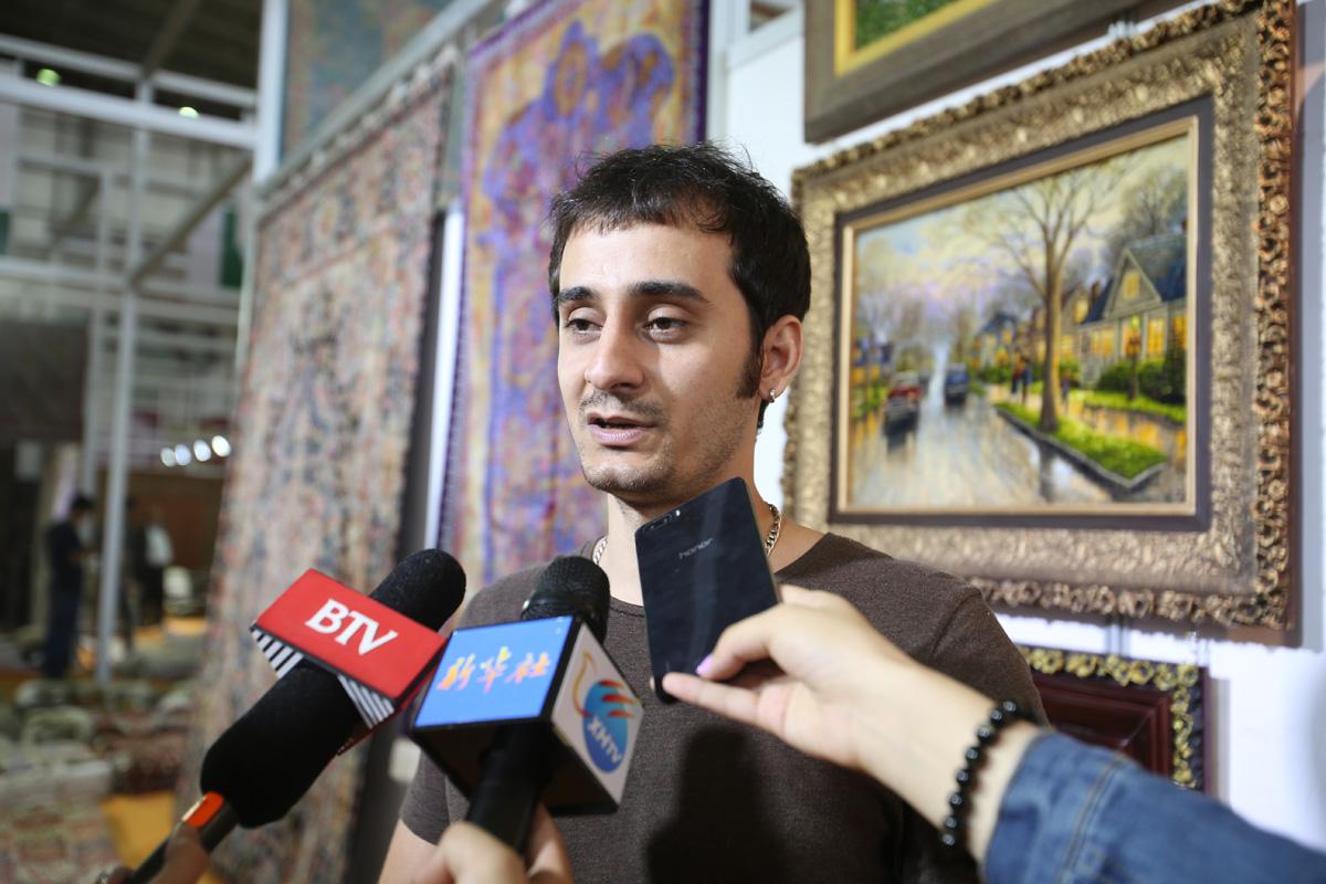 2015中国(青海)藏毯国际展览会布展现场采访伊朗展商。摄影:赵冰